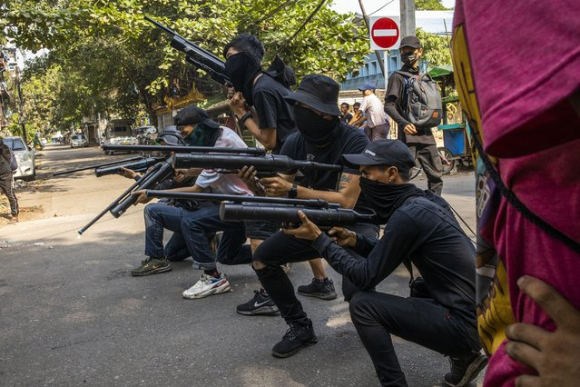 Anti-coup protesters line in formation with homemade air rifles during a demonstration against the military coup in Yangon, Myanmar, Saturday, April 3, 2021. Threats of lethal violence and arrests of protesters have failed to suppress daily demonstrations across Myanmar demanding the military step down and reinstate the democratically elected government. (Photo by AP Photo/Stringer)