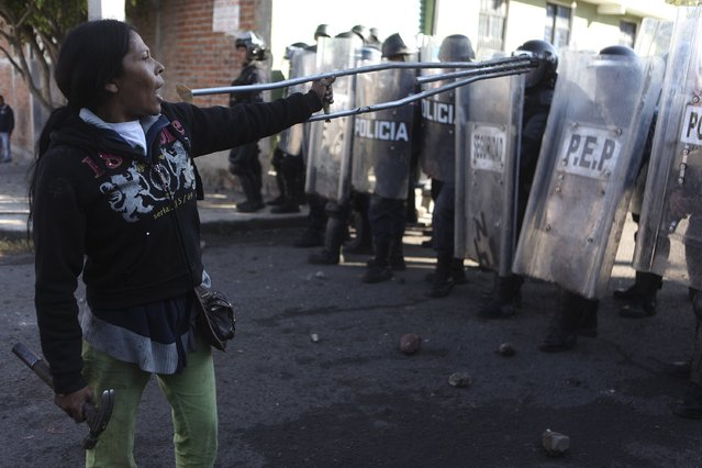A woman points at riot policemen with a crutch during an eviction at a squatter settlement in Morelia February 12, 2015. About 700 people from a squatter settlement were evicted, and their makeshift homes demolished early Thursday by state police officers, local media reported. (Photo by Alan Ortega/Reuters)