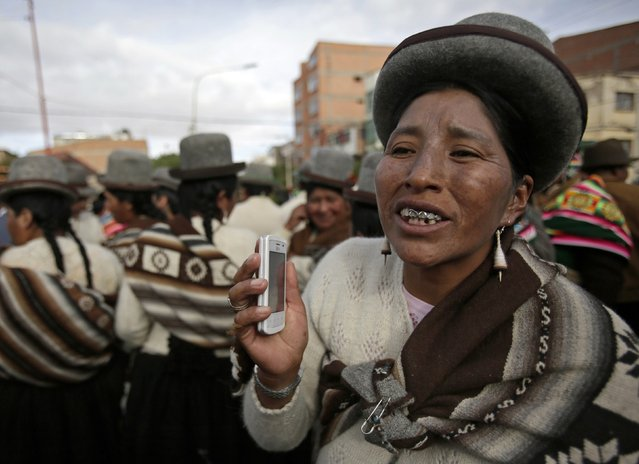 An indigenous woman holds a mobile phone during the Anata Andina (Andean carnival) parade in Oruro February 12, 2015. (Photo by David Mercado/Reuters)