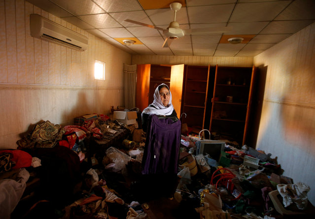 An Iraqi Kurdish woman looks on while inspecting her belongings inside her damaged house after returning to it in the town of Bashiqa which was retaken by Kurdish Peshmerga fighters following a battle with Islamic State militants, north of Mosul, Iraq November 29, 2016. (Photo by Mohammed Salem/Reuters)