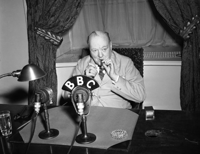 Prime Minister Winston Churchill lights up his cigar again before broadcasting a radio address to the British people from Washington on May 14, 1943. (Photo by Byron Rollins/AP Photo)