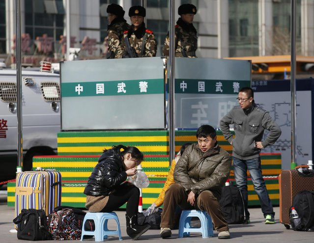 People sit on stools as they wait for their trains in front of paramilitary policemen at a railway station in Beijing February 16, 2015. (Photo by Kim Kyung-Hoon/Reuters)