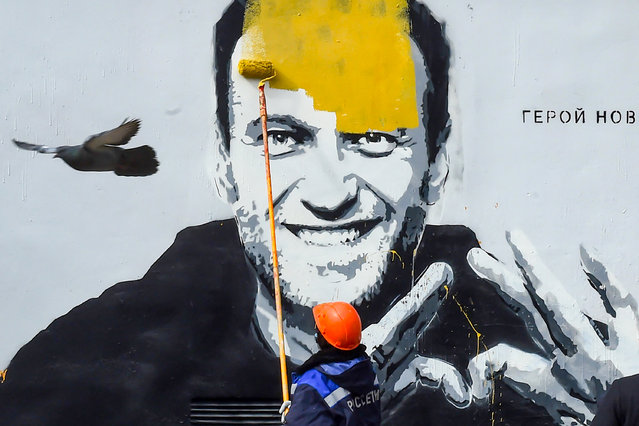 """Municipal workers paint over a graffiti depicting jailed Russian opposition politician Alexei Navalny with wordings reading, """"The hero of the new age"""", in St. Petersburg, Russia, 28 April 2021. Navalny is currently being held at a prison camp northeast of Moscow, sentenced to imprisonment at the penal camp in early February 2021 for violating parole requirements related to an earlier suspended sentence over 2014 embezzlement charges. (Photo by Olga Maltseva/AFP Photo)"""