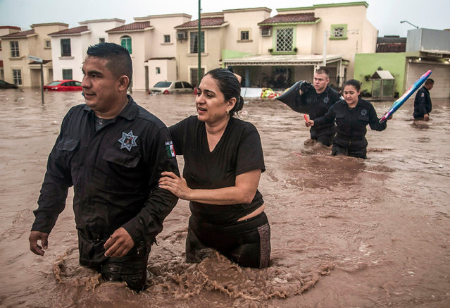 Police officers help a woman cross a flooded street in Culiacan, Sinaloa State, Mexico on September 20, 2018. Heavy rains have flooded different neighborhoods of Culiacan in the last hours. (Photo by Rashide Frias/AFP Photo)