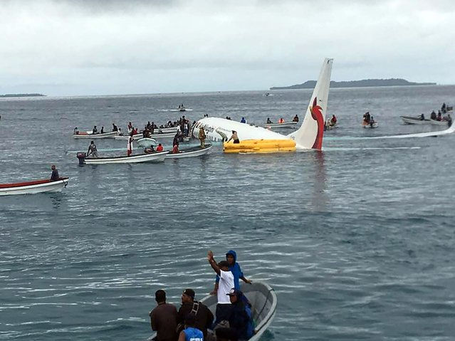 This picture taken by James Yaingeluo on September 28, 2018 shows locals approaching to rescue passengers of the crashed Air Niugini aircraft on the remote Island of Weno, in Micronesia. An Air Niugini aircraft ditched into a lagoon after overshooting the runway on the remote island of Weno but there were no serious injuries, local media reports said. (Photo by James Yaingeluo/AFP Photo)