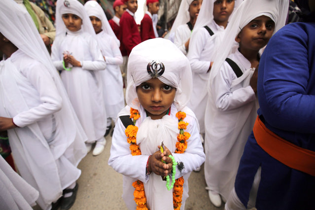 Indian children, wearing religious attire, take part in a religious procession on the eve of the 351st birth anniversary of the tenth Guru or master of the Sikhs, Sri Guru Gobind Singh in Amritsar, India, 15 January 2016. Guru Gobind Singh Ji was the tenth Sikh Guru who initiated the special order or sect of the Sikhs called the Khalsa Panth. (Photo by Raminder Pal Singh/EPA)