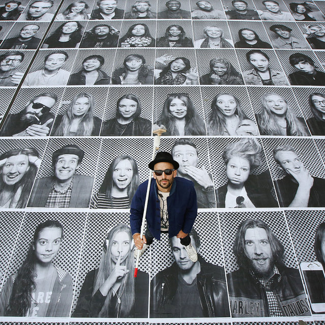 French artist JR poses with some of his giant portraits at Somerset House for his Inside Out project on October 7, 2013 in London, England. Displaying at the Lazarides gallery and also on hoardings at a building site opposite the Old Bailey, the exhibition is comprised of giant black and white images of members of the public who are photographed in a mobile studio mounted on the back of a small truck. The Inside Out photo booth truck is located on the River Terrace of Somerset House from 3rd – 11th October 2013.  (Photo by Peter Macdiarmid/Getty Images)