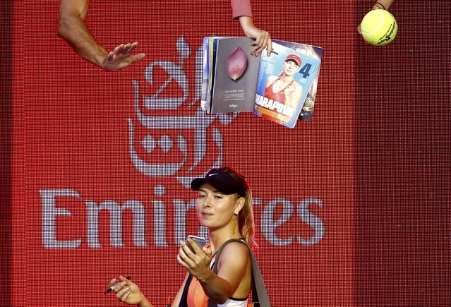 Russia's Maria Sharapova takes a selfie using a spectator's phone after winning her second round match against Belarus' Aliaksandra Sasnovich at the Australian Open tennis tournament at Melbourne Park, Australia, January 20, 2016. (Photo by Thomas Peter/Reuters)