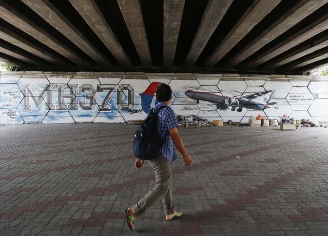 A man walks past graffiti depicting the missing Malaysia Airlines flight MH370 on the one year anniversary of its disappearance in Kuala Lumpur, March 8, 2015. Prime Minister Najib Razak said on Sunday Malaysia remains committed to the search for the missing MH370 jetliner a year after it vanished without trace and he is hopeful it will be found. REUTERS/Olivia Harris (MALAYSIA - Tags: TRANSPORT DISASTER ANNIVERSARY)