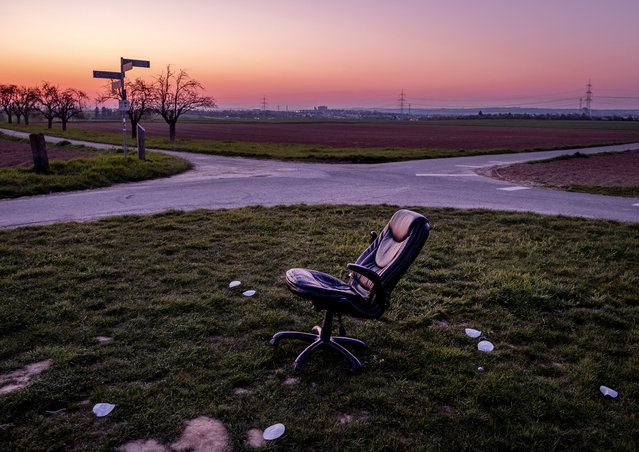 An office chair stands between small roads, fields and acres in the outskirts of Frankfurt, Germany, Wednesday, April 28, 2021. (Photo by Michael Probst/AP Photo)