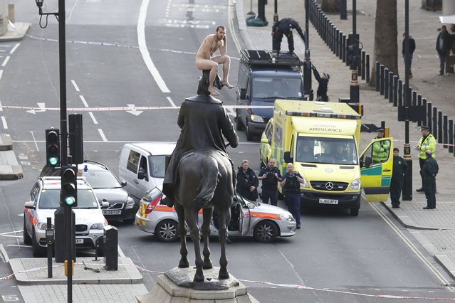 News Finalist – Justin Tallis. An unidentified man sits naked on top of the statue of Prince George, Duke of Cambridge outside the Ministry of Defence building in Whitehall in central London on November 23, 2012. The man, who brought Whitehall to a standstill for almost two hours, stood naked on the statue and struck various poses before being eventually talked down. (Photo by Justin Tallis/AFP Photo)