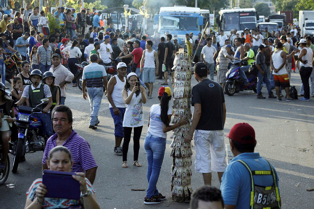 People take pictures next to a pole covered with 100-bolivar bills during a protest in El Pinal, Venezuela December 16, 2016. (Photo by Carlos Eduardo Ramirez/Reuters)