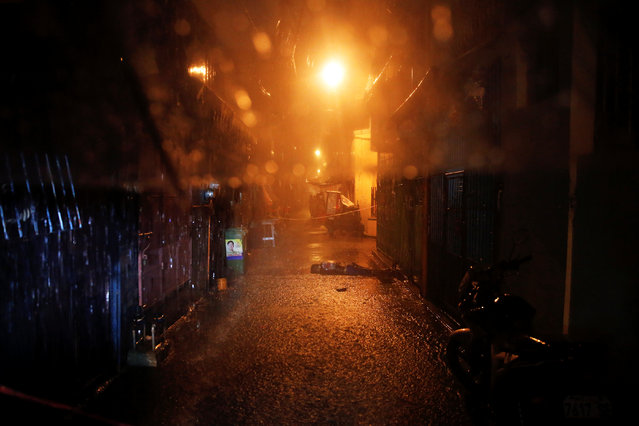 Heavy rain pours as the body of a man killed by unidentified gunmen riding motorcycles is left in a narrow alley in Manila, Philippines early October 11, 2016. (Photo by Damir Sagolj/Reuters)