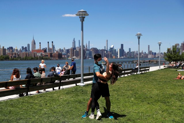 Felipe Beltran, 25, wears a protective face mask as he gives a salsa lesson to Brianna Davis, 29, amid coronavirus pandemic at Domino Park in the Williamsburg section of Brooklyn in New York City, June 16, 2021. (Photo by Shannon Stapleton/Reuters)