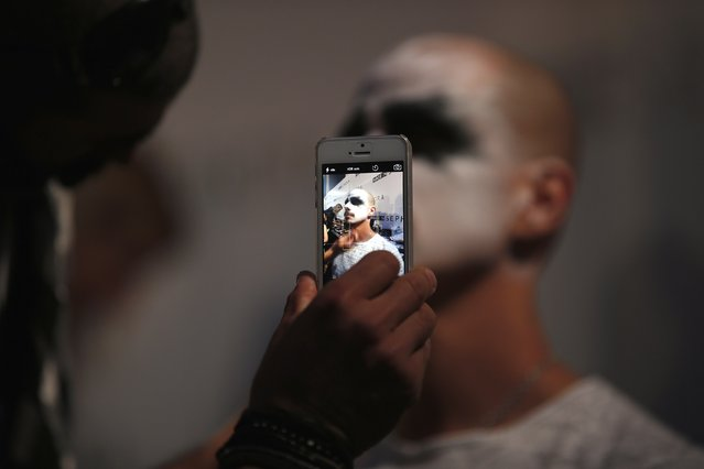 A model is pictured with a mobile phone as he is prepared before Nuno Gama show during Lisbon Fashion Week March 15, 2015. (Photo by Rafael Marchante/Reuters)