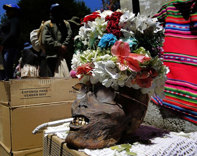 """A skull with its skin still intact is displayed during the """"Dia de los natitas"""" ceremony. (Photo by David Mercado/Reuters)"""