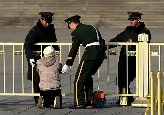 Paramilitary police officers stop a woman as she protests on her knees in front of the Great Hall of the People, where the annual session of China's legislature, the National People's Congress, is currently being held, in Beijing on March 13, 2015. Each year during the annual legislative session petitioners arrive in Beijing hoping to air their personal grievances with Chinese leaders, only to be led away and often returned to their hometowns by police. (Photo by Greg Baker/AFP Photo)