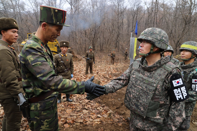 A South Korean military officer (R) and a North Korean military officer shake hands during an operation to reconnect a road across the Military Demarcation Line inside the Demilitarised Zone (DMZ) separating the two Koreas November 22, 2018. (Photo by The Defense Ministry/Yonhap via Reuters)