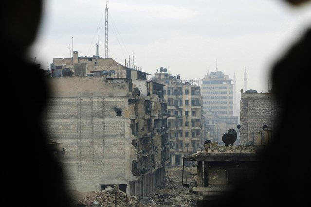 A view of a frontline is seen through a hole in the wall in Old Aleppo January 4, 2015. (Photo by Hosam Katan/Reuters)