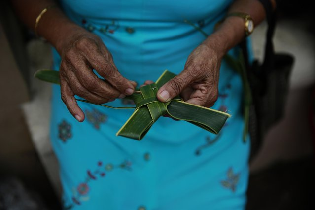 An Indian Christian devotee makes a cross with palm leaves after she arrived for the Palm Sunday mass at a Church in Mumbai, India, Sunday, March 29, 2015. (Photo by Rafiq Maqbool/AP Photo)