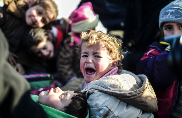 A Syrian child cries as Syrians fleeing the northern embattled city of Aleppo wait on February 5, 2016 in Bab-Al Salam, next to the city of Azaz near Turkish crossing gate in northern Syria. Nearly 40,000 Syrian civilians have fled a regime offensive near Aleppo, a monitor said, as Turkey warned it was bracing for a wave of tens of thousands of refugees. (Photo by Bulent Kilic/AFP Photo)