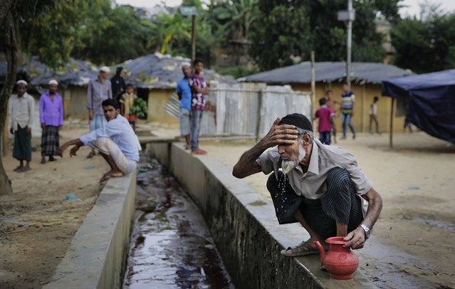 In this photograph taken August 24, 2018, Rohingya faith healer Abul Kalam performs ablution before offering prayers at a makeshift mosque in Kutupalong refugee camp, Bangladesh. (Photo by Altaf Qadri/AP Photo)