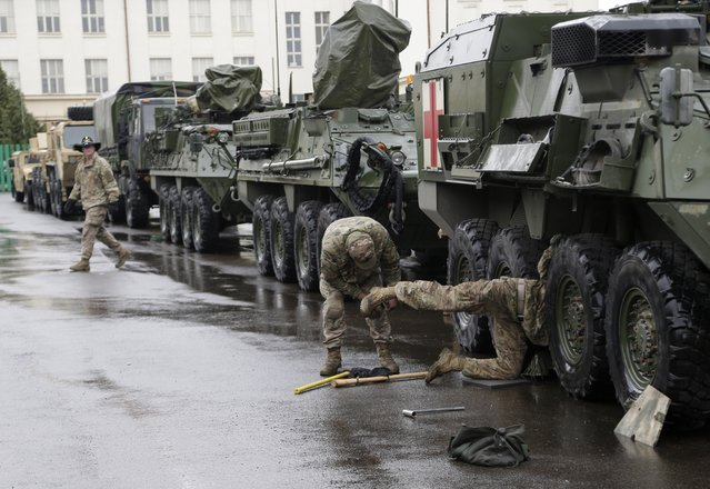 US army soldiers perform maintenance on a stryker armored vehicle during a stop of their convoy in Prague, Czech Republic, Tuesday, March 31, 2015. (Photo by Petr David Josek/AP Photo)