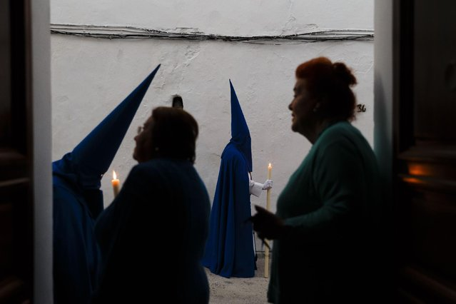 "Women look from their house door way as penitents take part in ""Nuestro Senor Atado a la Columna, Maria Santisima de la Paz y San Juan Evangelista"" Holy Week procession in Arcos de la Frontera, Spain, Tuesday, March 31, 2015. (Photo by Daniel Ochoa de Olza/AP Photo)"