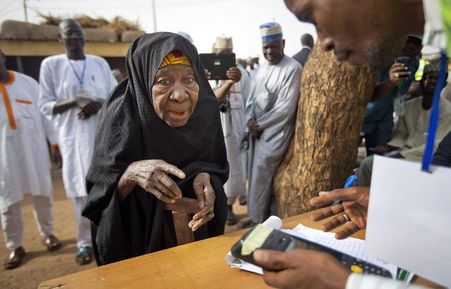 An elderly Nigerian woman arrives to validate her voting card using a fingerprint reader, prior to casting her vote later in the day, in the home town of opposition candidate Gen. Muhammadu Buhari, in Daura, Nigeria Saturday, March 28, 2015. Nigerians went to the polls Saturday in presidential elections which analysts say will be the most tightly contested in the history of Africa's richest nation and its largest democracy. (Photo by Ben Curtis/AP Photo)