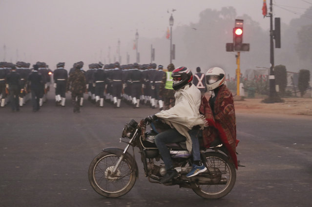 In this Wednesday, December 26, 2018, photo, a motorcyclist rides wearing pollution masks in New Delhi, India. Authorities have ordered fire services to sprinkle water from high rise building to settle dust particles and stop burning of garbage and building activity in the Indian capital as the air quality hovered between severe and very poor this week posing a serious health hazard for millions of people. (Photo by Manish Swarup/AP Photo)