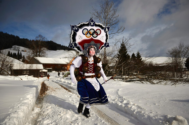 "A leader ""Rolli"" of a yodel group ""Schuppel"" runs in the snow in front of a farmstead during the ""Silvesterchlausen"" in the early morning in Urnaesch in the Swiss canton Appenzell Ausserroden on January 13, 2017. The ""Silvesterchlausen"" is a tradition of the Swiss canton Appenzell, where colorfull characters organized in groups called ""Schuppel"", chase out the old year and welcome the new one. They run all day long from farmstead to farmstead, gather together to sing a jodel and great the farmers. A ""Schuppel"" consists of some ""Schelli"" and two ""Rolli"", sometimes with female dresses and nice scenes over the head, despite the dress all participants are males. The Silversterchlausen run twice a year, first for the new Silvester on December 31, and then again on January 13, for the old Silvester following the Julian calendar. (Photo by Michael Buholzer/AFP Photo)"