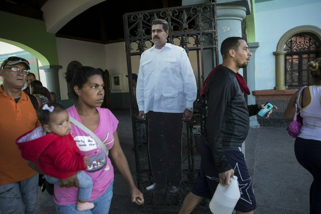 A cardboard life-size cut out of Venezuelan President Nicolas Maduro stands at the entrance of a public park in Caracas, Venezuela, Friday, January 25, 2019. Juan Guaido, the Venezuelan opposition leader who has declared himself interim president, appeared in public Friday for the first time in days and vowed to remain on the streets to usher in a transitional government, while President Nicolas Maduro dug in and accused his opponents of orchestrating a coup. (Photo by Rodrigo Abd/AP Photo)