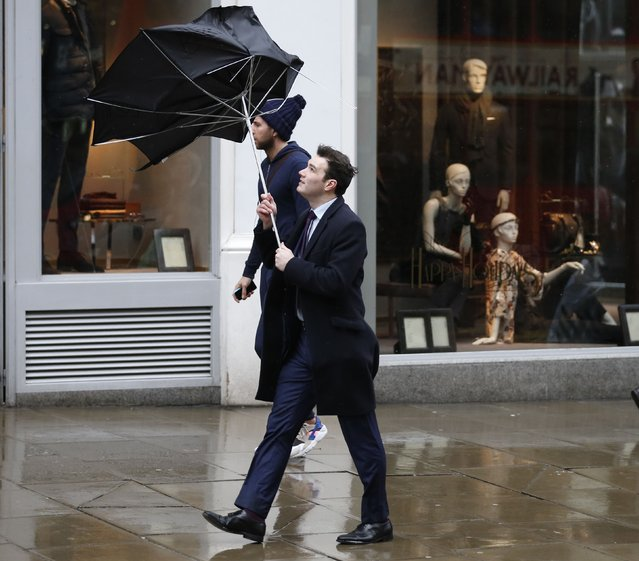 Pedestrians walk in wet and windy weather on Oxford Street in central London December 23, 2013. (Photo by Olivia Harris/Reuters)