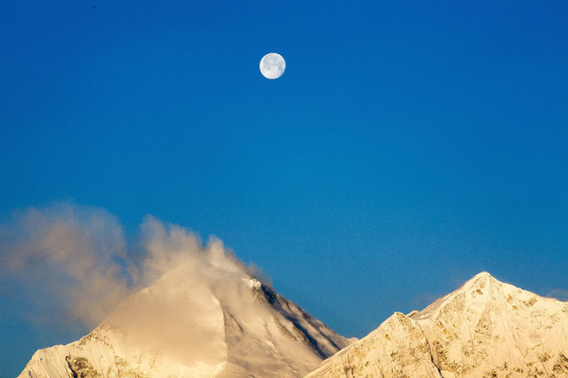 A picture made available on 09 April shows the moon setting while early morning sunlight lits up the Mt. Dhaulagiri, (L), 8,167 meters tall and 7th-highest mountain in the world, in Muktinaath at an altitude of 3800 meters in Mustang district, north east of Nepal, 05 April 2015. Mustang is the former kingdom of Lo, Nepal, located near to Tibet, China. (Photo by Narendra Shrestha/EPA)