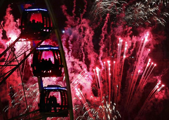 People ride a Ferris wheel as fireworks illuminate the sky over Edinburgh, Scotland. (Photo by David Cheskin/Press Association)