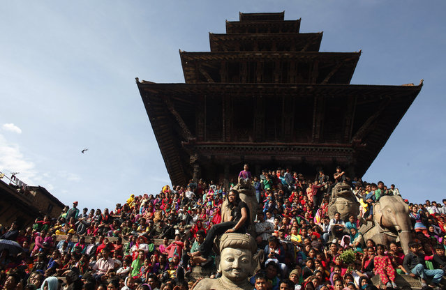 Nepalese people watch a concert organized ahead of the Sindur Jatra festival in Bhaktapur, Nepal, Tuesday, April 14, 2015. The festival is celebrated to welcome the advent of spring and the New Year. (Photo by Niranjan Shrestha/AP Photo)
