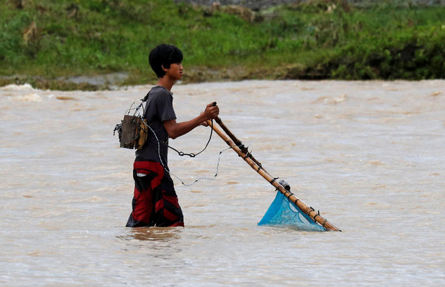 A man uses a net, operated by electricity from a car battery, to catch fish in a river a day after Typhoon Mangkhut hit Bambang, Nueva Vizcaya, in the Philippines, September 16, 2018. (Photo by Erik De Castro/Reuters)