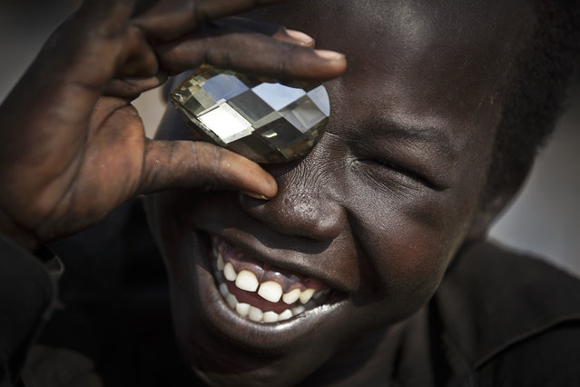 A displaced boy mimics the photographer taking a picture of him, using a fake plastic jewel, at a United Nations compound which has become home to thousands of people displaced by the recent fighting, in the capital Juba, South Sudan Sunday, December 29, 2013. (Photo by Ben Curtis/AP Photo)