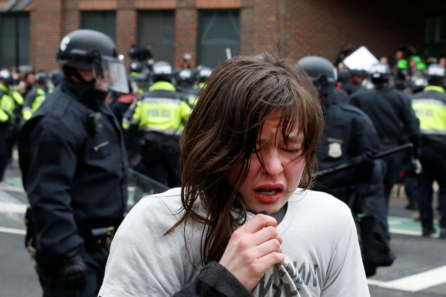An activist demonstrating against U.S. President Donald Trump reacts after being hit by pepper spray on the sidelines of the inauguration in Washington, DC, U.S., January 20, 2017. (Photo by Adrees Latif/Reuters)