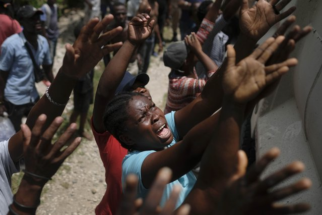 Earthquake victims reach for water being handed out during a food distribution in the Picot neighborhood in Les Cayes, Haiti, Sunday, August 22, 2021, eight days after a 7.2 magnitude earthquake hit the area. (Photo by Matias Delacroix/AP Photo)