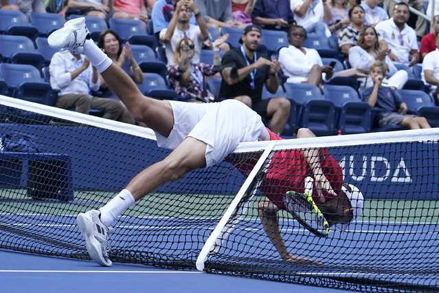 Oscar Otte, of Germany, falls over the net during his match against Matteo Berrettini, of Italy, in the fourth round of the US Open tennis championships, Monday, September 6, 2021, in New York. (Photo by Elise Amendola/AP Photo)