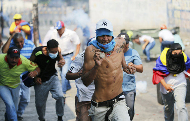 Demonstrators run from tear gas fired by Bolivarian National Guard officers during clashes in Urena, Venezuela, near the border with Colombia, Saturday, February 23, 2019. Venezuela's National Guard fired tear gas on residents clearing a barricaded border bridge between Venezuela and Colombia on Saturday, heightening tensions over blocked humanitarian aid that opposition leader Juan Guaido has vowed to bring into the country over objections from President Nicolas Maduro. (Photo by Fernando Llano/AP Photo)