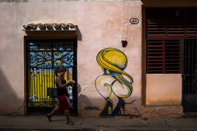 A woman passes by a closed art store decorated by a mural in Havana, Cuba, Wednesday, December 5, 2018. After weeks of public debates and overlapping complaints from artists and intellectuals about a decree that increased control for artists and promoters, Cuban authorities are about to publicize complementary rules that limit the power of cultural inspectors and limit official action about creation. (Photo by Desmond Boylan/AP Photo)