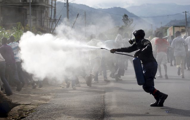A riot police officer sprays teargas on residents participating in street protests against the decision made by Burundi's ruling National Council for the Defence of Democracy-Forces for the Defence of Democracy (CNDD-FDD) party to allow President Pierre Nkurunziza to run for a third five-year term in office, in the capital Bujumbura, April 26, 2015. (Photo by Thomas Mukoya/Reuters)