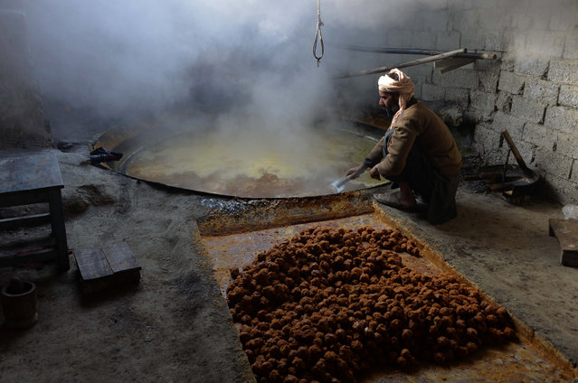 In this photograph taken on December 26, 2018, an Afghan laborer prepares brown sugar from sugarcane juice at a traditional factory in the Kama District of Nangarhar Province, east of Jalalabad. (Photo by Noorullah Shirzada/AFP Photo)