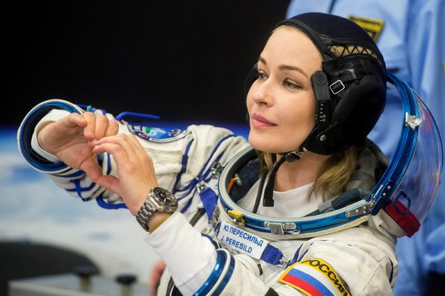This handout photo taken and released on October 5, 2021 by Russian Space Agency Roscosmos shows Russian crew member, actress Yulia Peresild forming a heart with her hands as her spacesuit is tested prior to the launch onboard the Soyuz MS-19 spacecraft at the Russian-leased Baikonur cosmodrome. (Photo by Andrey Shelepin/Russian Space Agency Roscosmos/AFP Photo)