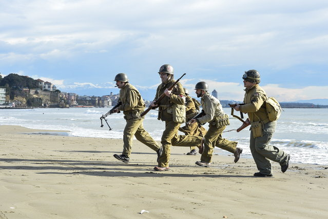 World War II enthusiasts wearing WWII garbs walk on Anzio beach, 52 km south of Rome, during a re-enactament to mark the 70th anniversary of the Allied landings in Italy, on January 25, 2014. (Photo by Andreas Solaro/AFP Photo)