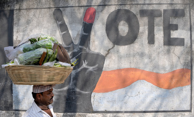 A vegetable vendor walks past graffiti urging Indians to vote, in Mumbai on February 3, 2017. Five Indian states representing more than 160 million voters will go to the polls, a key test for the prime minister after his shock currency move. The elections will begin on February 4, nearly three months after Modi announced he was scrapping nearly 86 percent of all Indian currency, a move aimed at curbing widespread tax evasion. (Photo by Indranil Mukherjee/AFP Photo)