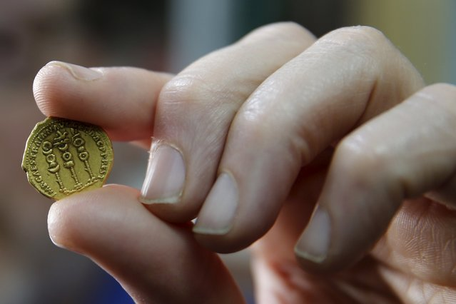 A nearly 2000 year-old gold coin with symbols of the Roman legions next to the name of the ruler Trajan on the one side and with an image of Emperor Augustus on the other side, is displayed for members of the media in the Israel Museum in Jerusalem March 14, 2016. Israel's Antiquities Authority (IAA) said on Monday that the coin is a very rare find as the only other similar coin known to exist is at the British Museum. (Photo by Ammar Awad/Reuters)