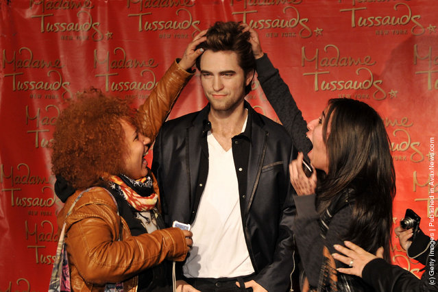 Fans pose for photographs with the Robert Pattinson wax figure